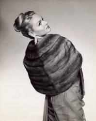 Jeune femme elegante posant de dos, elle est enveloppee dans un chale de fourrure. (anonyme) - Muzeo.com
