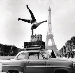 UN GLOBE-TROTTER ACROBATE DEVANT LA TOUR EIFFEL 1956 (KEYSTONE-FRANCE) - Muzeo.com