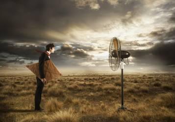 Homme d'affaires tenant un cerf-volant et regardant un ventilateur (Anderson Colin) - Muzeo.com