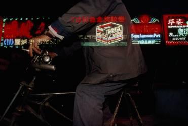 Homme à vélo passant les néons de la rue (Chesley Paul) - Muzeo.com