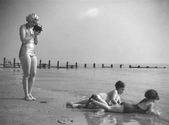 Femme en maillot de bain filmant les enfants au bord de la mer (anonyme) - Muzeo.com