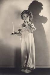 L'actrice americaine enfant Shirley Temple (nee en 1928) en chemise de nuit portant une bougie et posant le doigt sur sa bouche (silence chut) 1936 (anonyme) - Muzeo.com