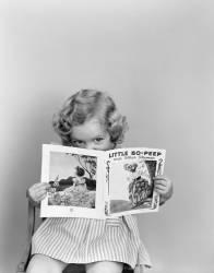 Petite fille des années 40 jetant un coup d'oeil au dessus du livre Little Bo-Peep (Roberts H. Armstrong) - Muzeo.com