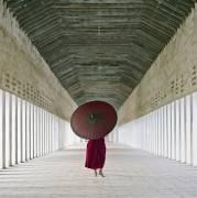 Buddhist monk standing in corridor holding traditional umbrella in Burma (Puddy Martin) - Muzeo.com